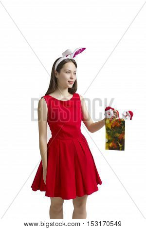 Funny woman in a bunny suit. Woman on a white background. Winter concept of advertising information. Good New Year spirit. Rabbit woman. with Christmas gift in hand.