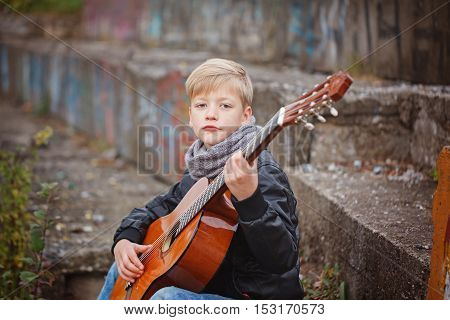 Little Boy Playing Guitar In Autumn Cold Day.  Children's Intere