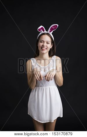 Cute happy girl wearing a white dress and bunny ears holding gift boxes. The rabbit costume on a black background.
