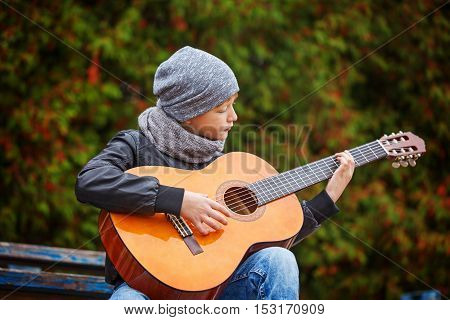 Little boy playing guitar on nature background. Children's interest in music