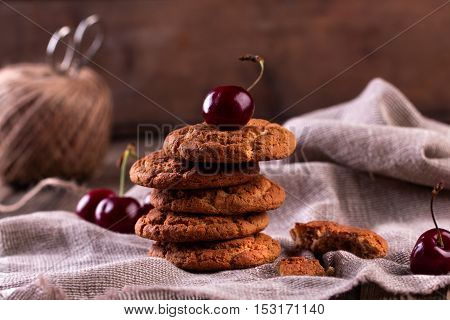Oatmeal cookies with cherry and chocolate on sackcloth
