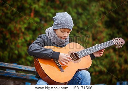 Little boy playing guitar in autumn cold day. He is dressed in a black leather jacket hat and scarf. Children's interest in music