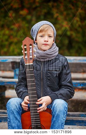 Cute little boy with guitar in autumn day. He is dressed in a black leather jacket hat and scarf.