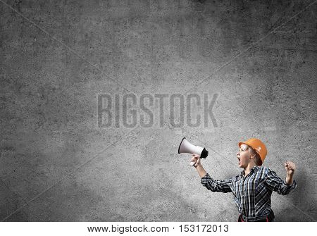 Engineer woman screaming in megaphone against concrete wall background