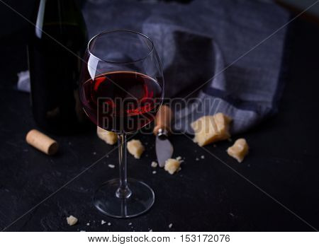 Wine bottle, glass of red wine, cheeses and cheese knife on black background