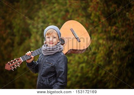 Cute little boy with guitar in nature background. He is dressed in a black leather jacket hat and scarf. He dreams of becoming a famous guitarist.