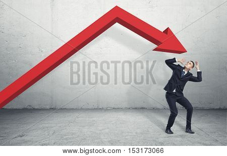 Businessman standing on the floor in a desparate pose under the giant red arrow aiming down at him, on the grey background. Business and management. Problems and failures. Dealing with crisis.