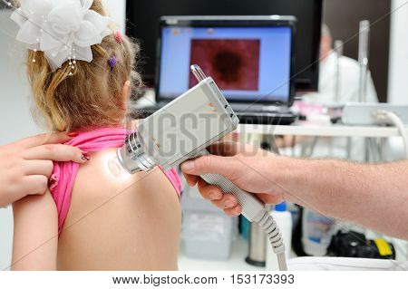 the doctor examines the special medical device moles child