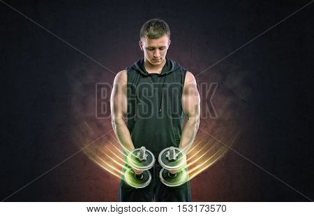 Cropped portrait of muscled young man working out with dumbbells with glowing streams of air. Self improvement and bodybuilding. Sport and fitness.