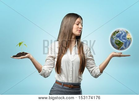 A woman holding a handful of soil with a plant in one hand and a globe in the other on the light-blue background. Environment and sustainability. Finding balance. Ecological problems. Elements of this image are furnished by NASA.