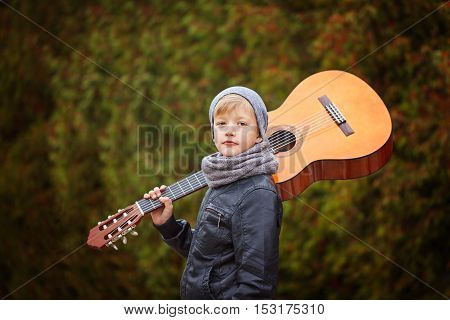 Cute little boy with guitar in nature background. He is dressed in a black leather jacket hat and scarf.