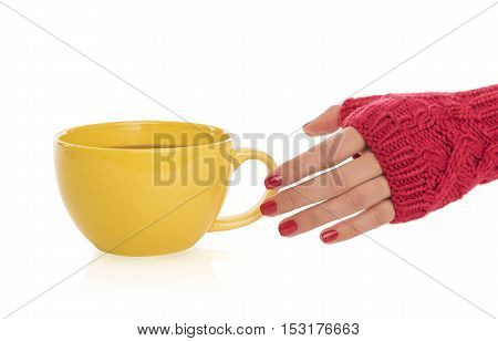 Female hand in a mitten reaches for a cup of tea on a white background.