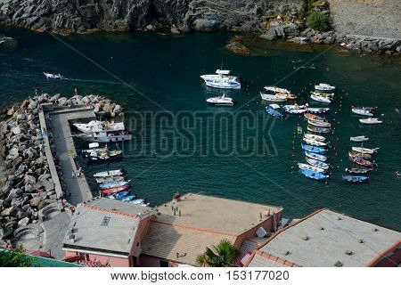 Vernazza Italy - September 4 2016: Boats in small port in Vernazza city in Liguria Italy. One of five Cinque Terre cities (unesco world heritage). Unidentified people visible.