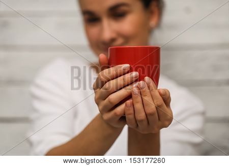 Beautiful young girl dressed in a white jacket with a red Cup in handcloseup