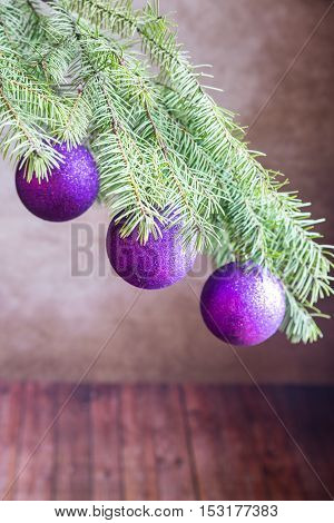 Christmas tree branch with ornaments on the wooden background