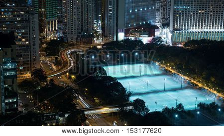 Night Hong Kong. City view with urban architecture, illuminated football fields and transport traffic on the roads
