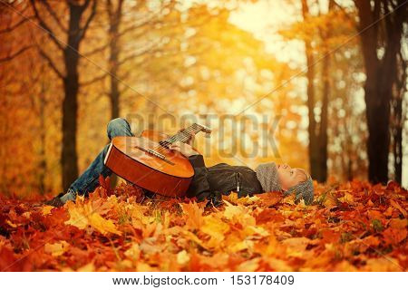 Cute boy with guitar lying on the grass in autumn sunny day.