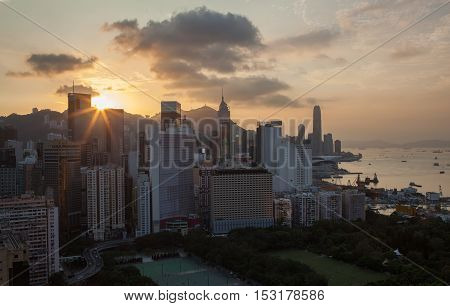 Hong Kong panorama at sunset. Cityscape with high-rise buildings and water transport traffic in the harbour
