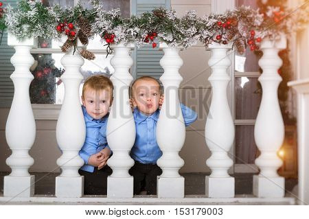 Two cute boy kid playing on porch decorated in Christmas style. Waiting for New year in festive interior with garland of snow-covered pines