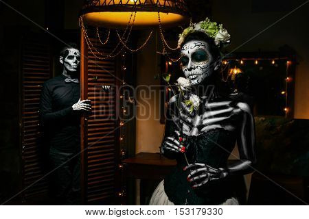 Portrait of a dead couple. Skeleton coming from a cupboard and woman with flower