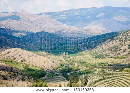 Views of hilly landscape with mountains and blue cloudy sky