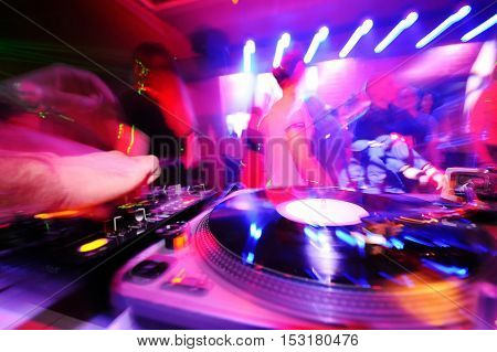 DJ behind the decks in a nightclub. DJ spinning plate. people dancing in a nightclub. disco