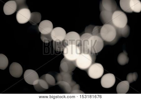 De-focused lights in the dark. Blurred spots of decoration bokeh shot. Vintage rich black and creamy white.