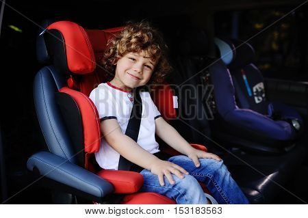 baby boy with curly hair sitting in red child car seat in a minivan.