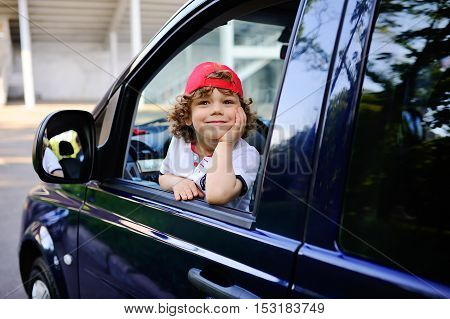 child with curly hair and a red cap sits behind the wheel of a car. baby boy grimaces in car window