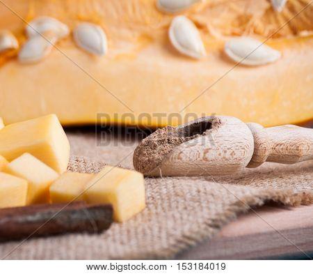 Ripe cut pumpkin and cinnamon on wood desk. Food background