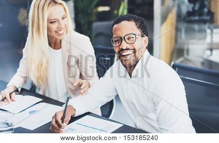 Two young coworkers working together in a modern office.Man wearing glasses, looking at the camera and smiling.Woman discussing with colleague new project.Horizontal, blurred background.