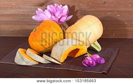 Pumpkin and flowers - violet autumn crocuses. Three grades of pumpkin with an orange and gray peel one of them is cut by pieces on a wooden table. The bouquet of autumn crocuses costs in a glass vase one flower on a table