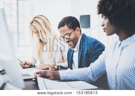 Three young coworkers working together in a modern office.Man wearing glasses and making notes with colleague on documents.Horizontal, blurred background.