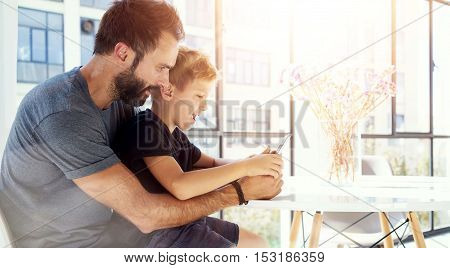 Young boy sitting with father at the table and playing together pc tablet in modern loft. Horizontal, blurred background. Sunlights effect