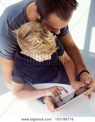 Young boy sitting with father at the table and playing together pc tablet in modern loft. Vertical, blurred background. Top view