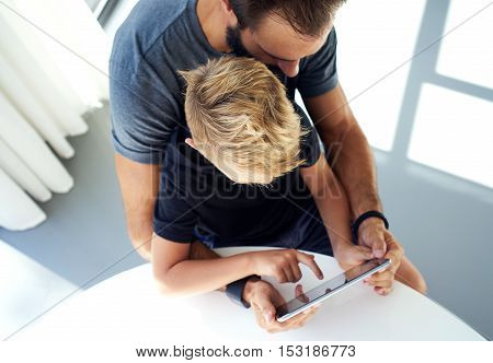 Young boy sitting with father and touching screen of pc tablet in sunny modern loft. Horizontal, blurred background. Top view