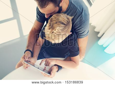 Young boy sitting with father and touching screen of pc tablet in sunny modern loft. Horizontal, blurred background. Top view, sunlights effect