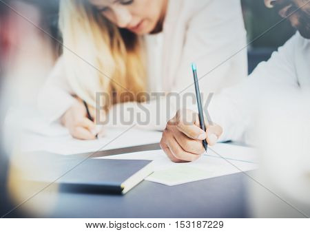 Two young coworkers working together in a modern office and making notes on documents.Closeup of pen holding in hands.Horizontal, blurred background.