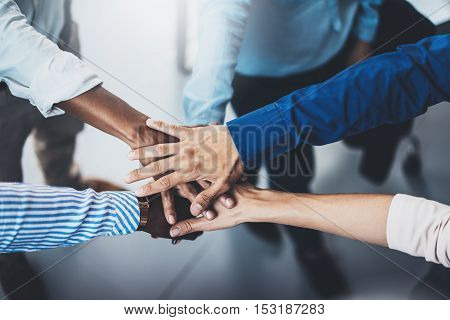 Concept of teamwork.International business team showing unity with their hands together. Horizontal, blurred background.