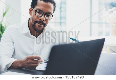 Dark skinned coworker wearing glasses and using laptop in modern office.African american man in white shirt working on workplace.Horizontal, blurred background.