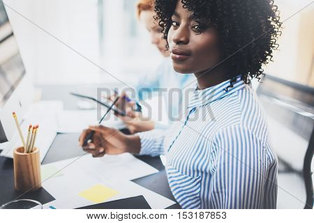 Young attractive african woman smiling and looking at the camera in modern office.Coworkers teamwork concept. Horizontal, blurred background