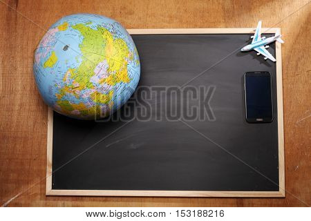 globe and toy airplane on top of blackboard
