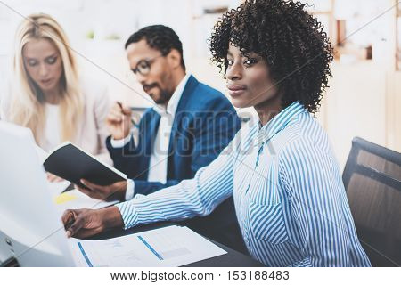 Group of business partners working together on online banking project in modern office.Young attractive african woman smiling at workplace, teamwork concept. Horizontal, blurred background