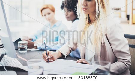 Beautiful blonde woman signing documnet on workplace in office. Group of girls coworkers discussing together business project. Horizontal, blurred background