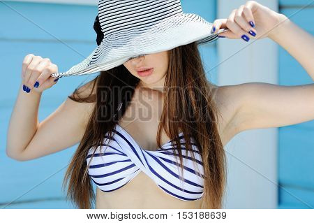 beautiful girl in a striped bathing suit and a striped hat with large fields on a blue background