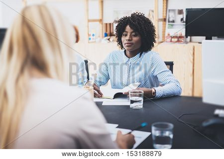 Beautiful womans making business meeting in modern office. Group of girls coworkers discussing together new business project. Horizontal, blurred background