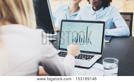 Beautiful blonde woman working modern laptop in office. Female hand pointing to the computer screen. Group of girls coworkers discussing together new fashion project. Horizontal, blurred background
