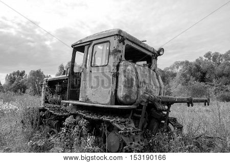 Old abandoned rusted tractor stands on grass. Black and white photography