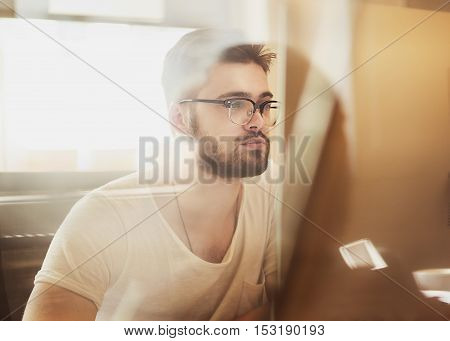 Happy young man wearing glasses as he works on his laptop to get all his business done early in the morning employee looking at computer monitor during working day in office. double exposure.