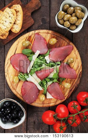 Italian bresaola, cured beef slices with grana padano cheese and rocket salad